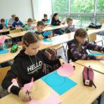 Kilkoro dzieci siedzi wławkach iwycina figury geometryczne zpapieru.