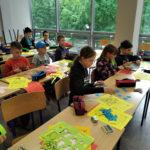 Kilkoro dzieci siedzi wławkach irozwiązuje zadania zwycinakami matematycznymi.