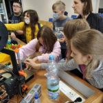 Kilkoro dzieci stoi przy drukarce 3D ipoznaje jej działanie.