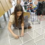 Kilkoro dzieci siedzi napodłodze ibuduje figury geometryczne.