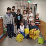 Kilkoro dzieci pokazuje zbudowane przezsiebie figury geometryczne zklocków konstrukcyjnych.
