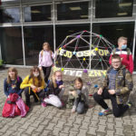 """Grupa dzieci stoi przedbudynkiem obok dużej figury geometrycznej znapisem ,,Kalejdoskop Matematyczny""""."""