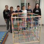 Kilkoro dzieci stoi zadużym sześcianem zbudowanym zklocków konstrukcyjnych.