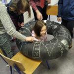 Grupa dzieci rysuje kredami naoponie.