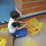 Chłopiec buduje zklocków konstrukcyjnych sześcian.