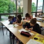 Dzieci rysują iwycinają zpapieru figury geometryczne.