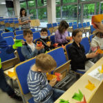 Dzieci budują figury geometryczne zpapieru.