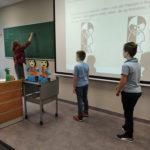 """Dwóch chłopców stoi przy tablicy – reszta dzieci rozwiązuje zagadkę matematyczną ,,Kto zwaszej dwójki jest Paputem akto Trolinkiem"""""""