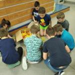 Grupa dzieci siedzi wkręgu ibuduje figury zklocków konstrukcyjnych